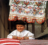 A little boy from Sumiac, laughing on mothers pillow. A photography from the book The Folk Treasury of Slovakia.